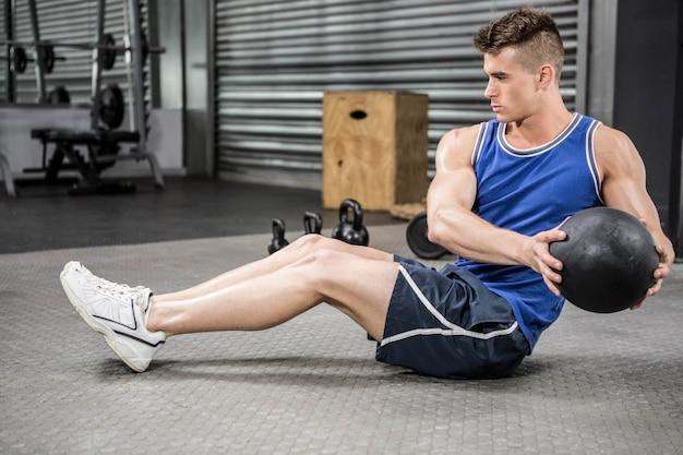 Hombre musculoso entrenando con balón medicinal en el gimnasio de crossfit