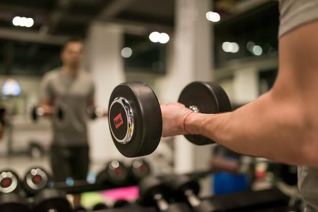 Hombre musculoso entrenando con pesas rojas en el gimnasio