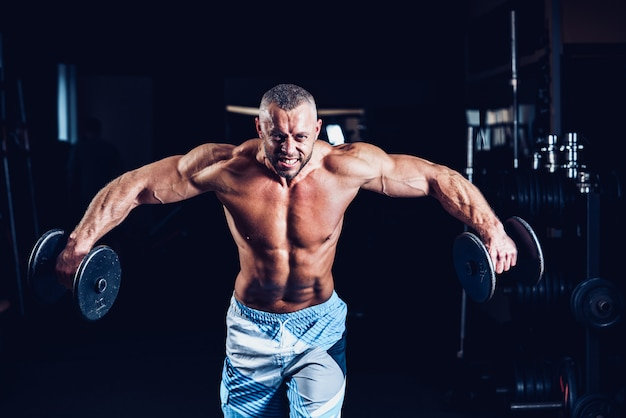Hombre musculoso entrenando sus hombros con pesas en el gimnasio