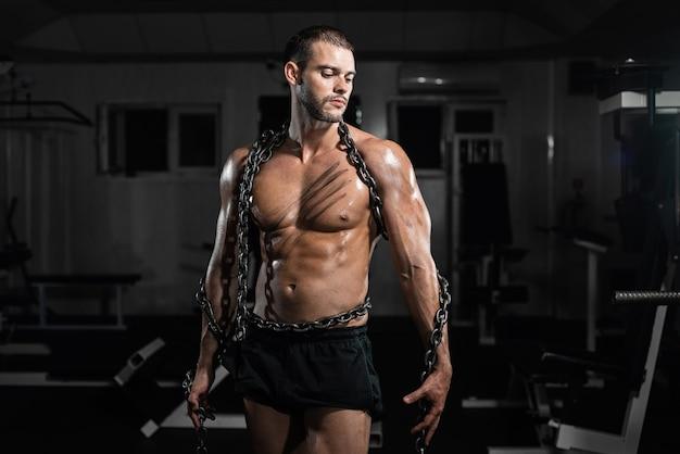 Hombre musculoso esclavo encadenado en gimnasio, el prisionero.