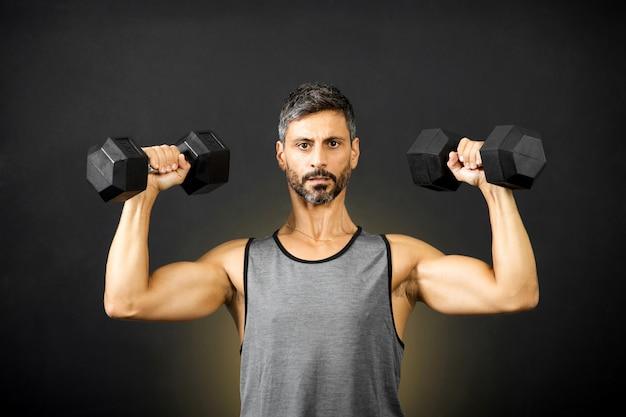 Hombre musculoso en forma de pesas con pesas