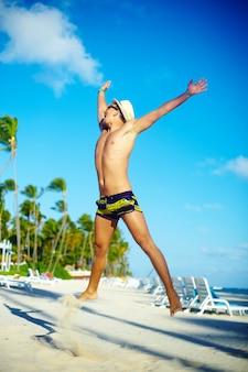 Hombre musculoso guapo feliz en sombrero para el sol en la playa saltando detrás del cielo azul detrás del cielo azul
