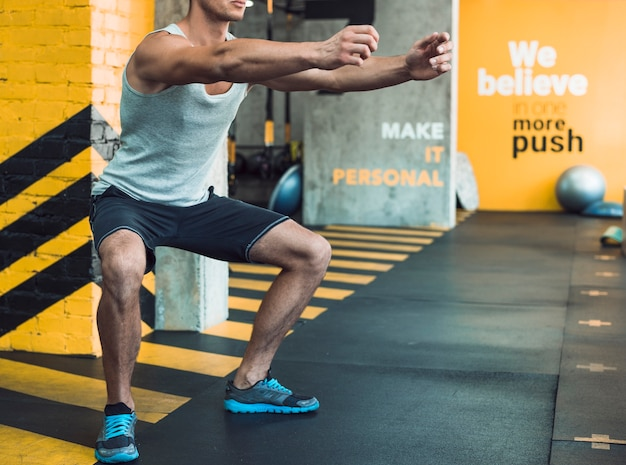 Hombre musculoso haciendo ejercicios de calentamiento en el gimnasio