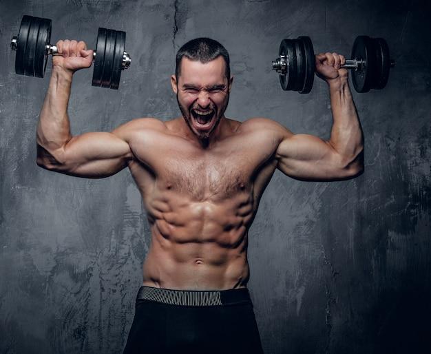 Hombre musculoso haciendo ejercicios de hombro