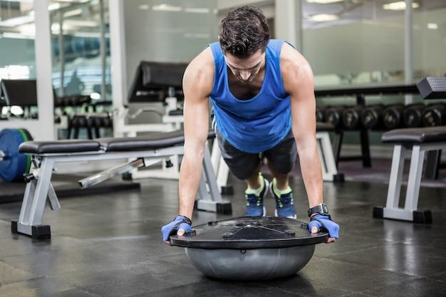 Hombre musculoso haciendo empujar hacia arriba con la bola bosu en el gimnasio