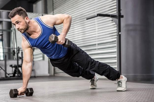 Hombre musculoso haciendo empujar hacia arriba con pesas en el gimnasio de crossfit