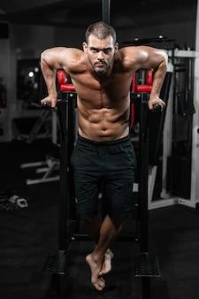Hombre musculoso haciendo flexiones en barras irregulares en el gimnasio de crossfit