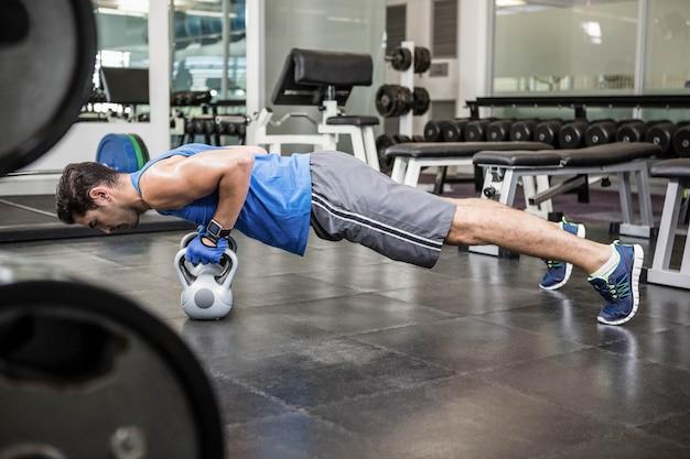 Hombre musculoso haciendo flexiones con pesas en el gimnasio