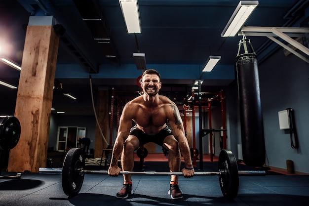 Hombre musculoso haciendo peso muerto una barra en el moderno gimnasio. entrenamiento funcional.