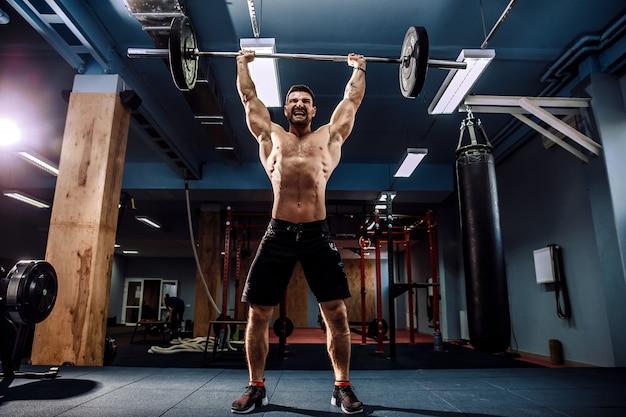 Hombre musculoso haciendo peso muerto una barra sobre su cabeza en el moderno gimnasio. entrenamiento funcional.