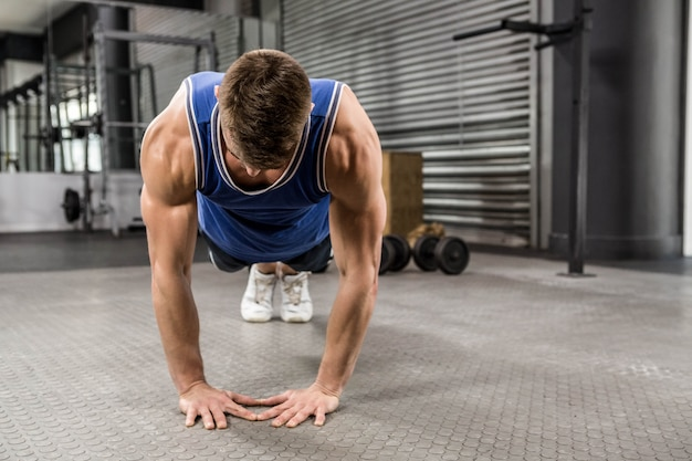 Hombre musculoso haciendo push up en el gimnasio de crossfit