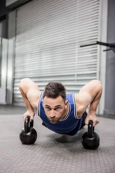 Hombre musculoso haciendo push up con kettlebells en el gimnasio de crossfit