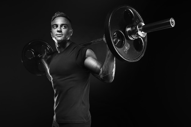 Hombre musculoso haciendo sentadillas con pesas sobre la cabeza