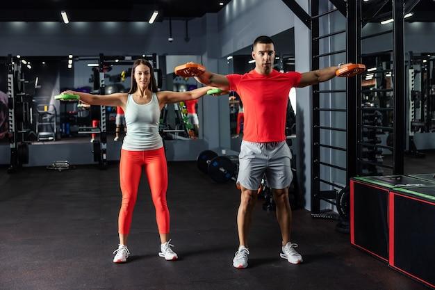 Un hombre musculoso y una hermosa joven haciendo algunos ejercicios de brazos y hombros juntos en el gimnasio cubierto por la noche
