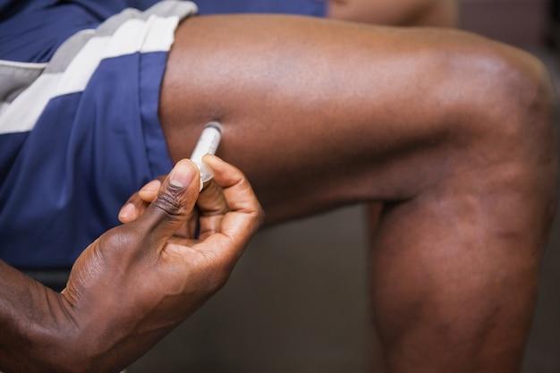 Hombre musculoso inyectando esteroides