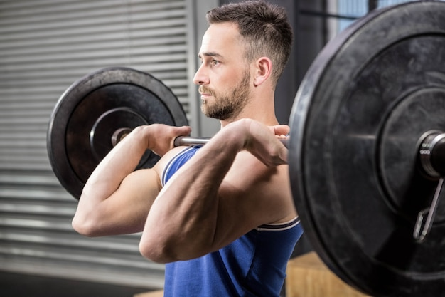 Hombre musculoso levantando barra en el gimnasio de crossfit