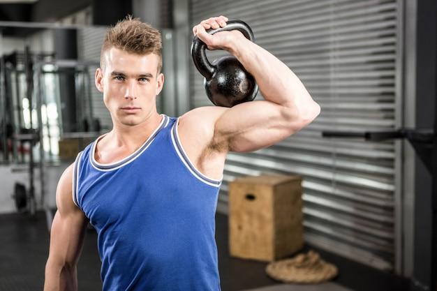 Hombre musculoso levantando pesas pesadas en el gimnasio de crossfit