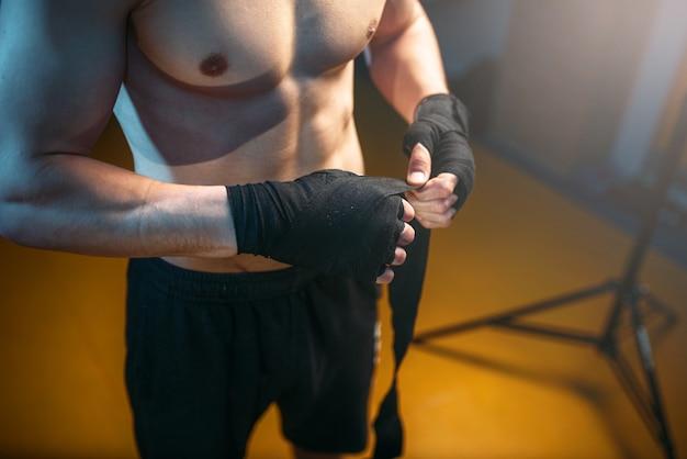 Hombre musculoso manos en vendas negras