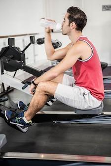 Hombre musculoso en la máquina de remo de agua potable en el gimnasio
