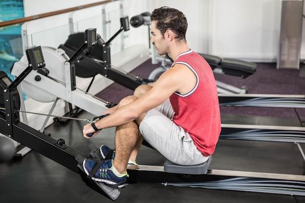 Hombre musculoso en la máquina de remo en el gimnasio