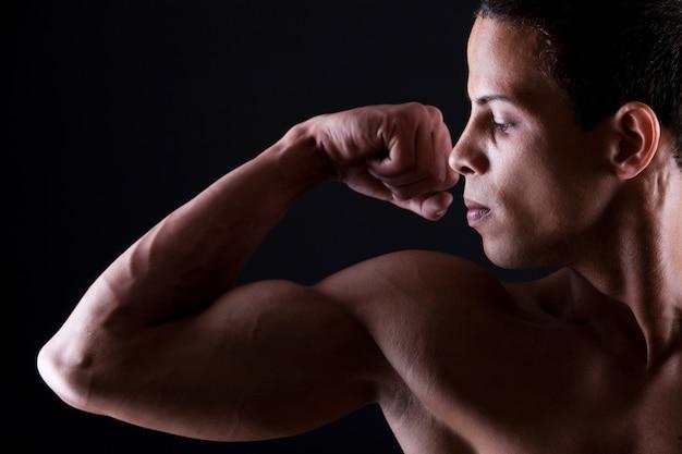 Hombre musculoso mostrando sus bíceps fuertes