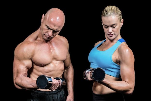 Hombre musculoso y mujer concentrando al levantar pesas