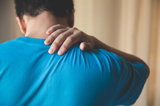 Hombre musculoso que sufre de dolor de espalda y cuello. problemas incorrectos de postura sentada espasmos musculares, reumatismo. alivio del dolor, concepto quiropráctico. lesiones por ejercicio deportivo