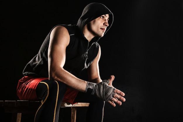 El hombre musculoso sentado y descansando sobre negro