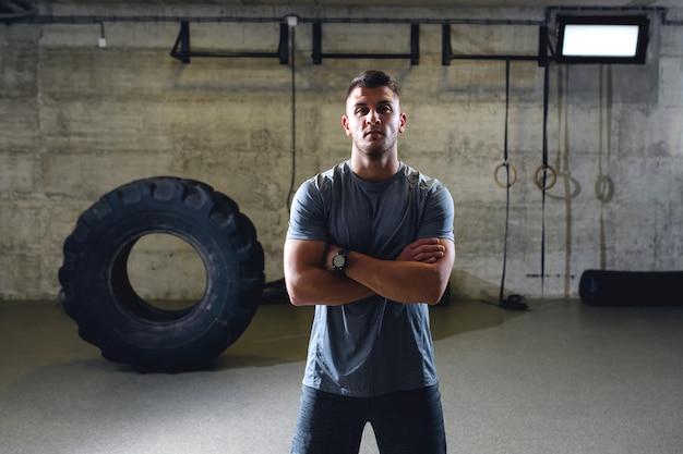 Hombre musculoso serio en ropa deportiva de pie con los brazos cruzados en el gimnasio cross-fit.
