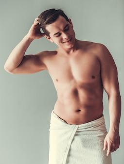 Hombre musculoso sexy con el pecho desnudo envuelto en una toalla blanca.