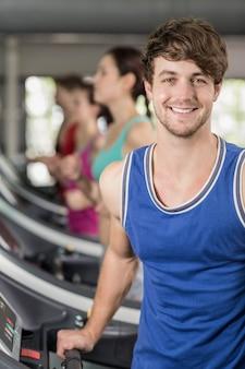 Hombre musculoso sonriente en cinta en el gimnasio