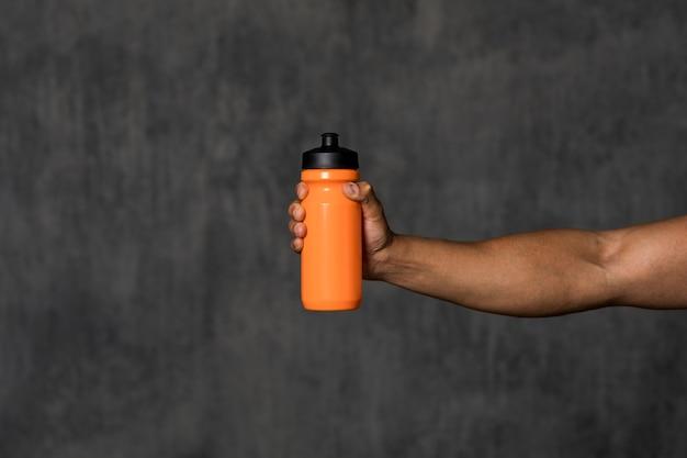 Hombre musculoso sosteniendo una botella de agua naranja