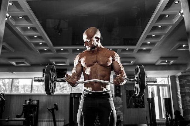 Hombre musculoso trabajando en el gimnasio haciendo ejercicios con pesas