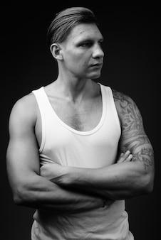 Hombre musculoso vistiendo camiseta blanca contra la pared negra