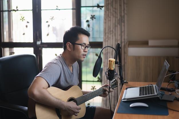 Hombre músico grabando música en el estudio de música en casa