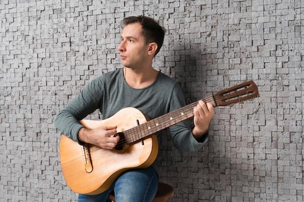 Hombre músico en el interior tocando la guitarra clásica