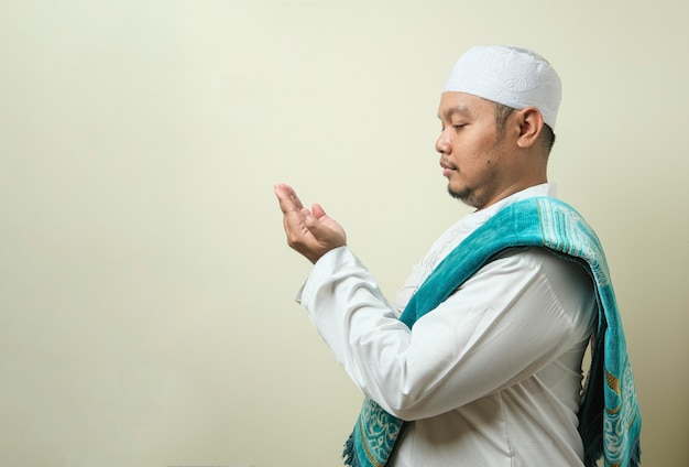 Hombre musulmán asiático gordo rezando con un espacio vacío junto a él