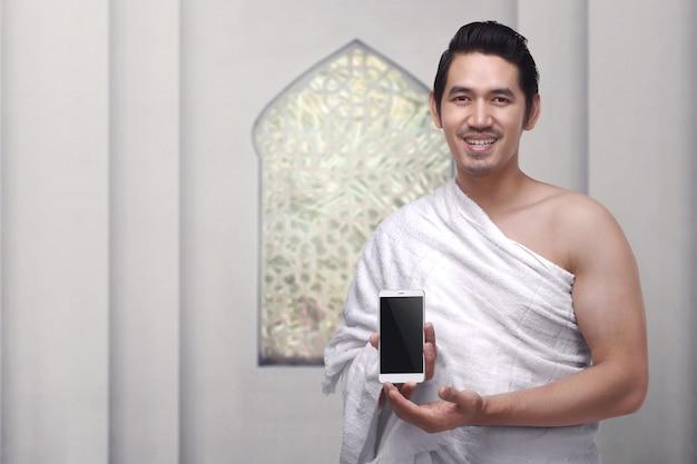 Hombre musulmán asiático hermoso que lleva la ropa del ihram que sostiene el teléfono móvil