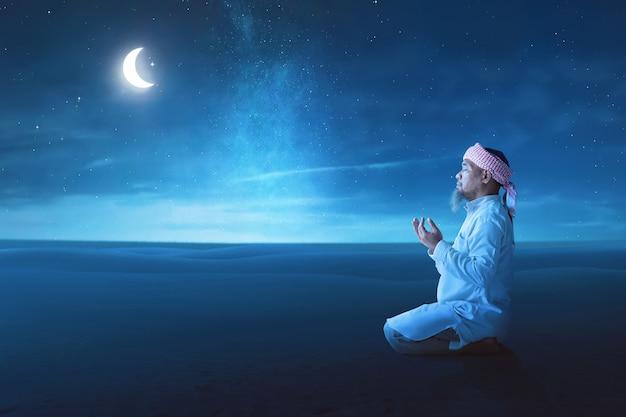 Hombre musulmán asiático mayor levanta la mano y rezando