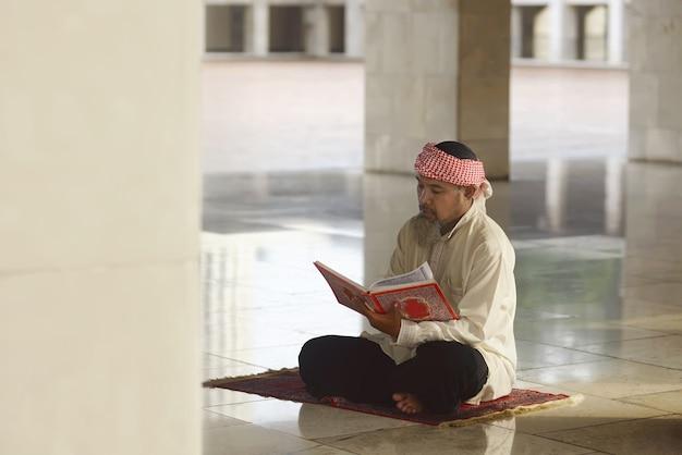 Hombre musulmán asiático mayor leyendo el corán