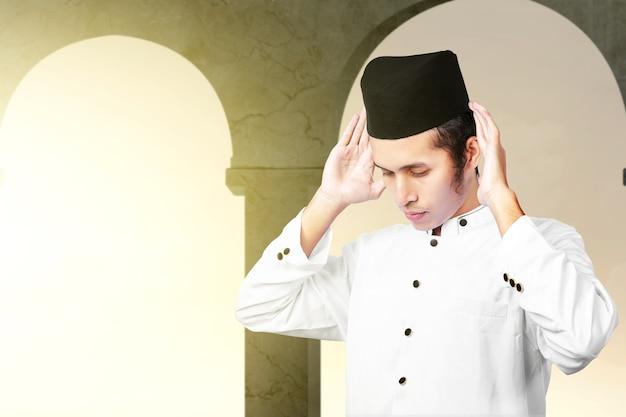 Hombre musulmán asiático en posición de oración (salat) en la mezquita