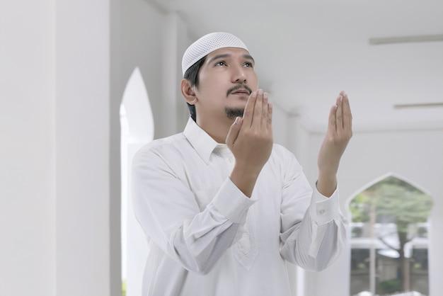 Hombre musulmán asiático religioso con gorra blanca rezando