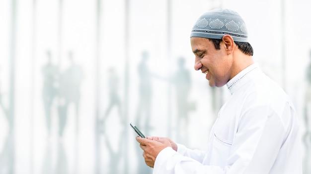 Hombre musulmán enviando mensajes de texto en su teléfono