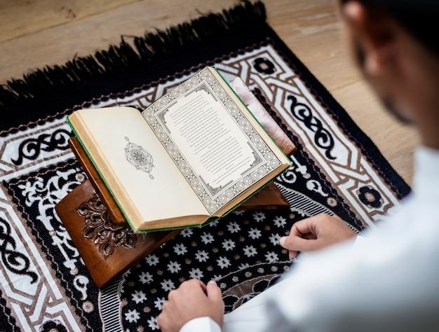Hombre musulmán estudiando el corán
