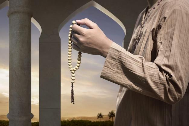 Hombre musulmán rezando con cuentas de oración
