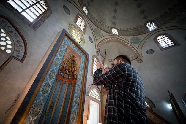 Hombre musulmán rezando dentro de la mezquita con las manos en alto