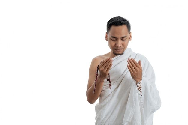 Hombre musulmán rezando en ropa blanca tradicional