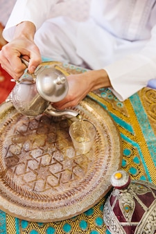 Hombre musulmán sentado en mesa con té