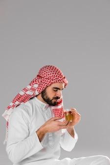 Hombre musulmán sonriente disfruta retrato tradicional de té