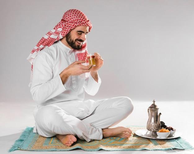 Hombre musulmán sonriente disfruta de té tradicional